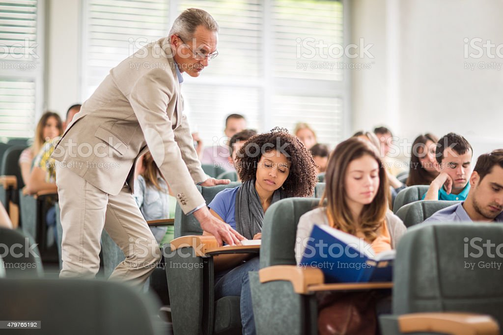 Teacher assisting African American student in the classroom. stock photo