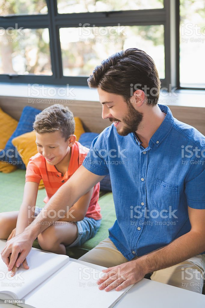 Teacher assisting blind student in library stock photo
