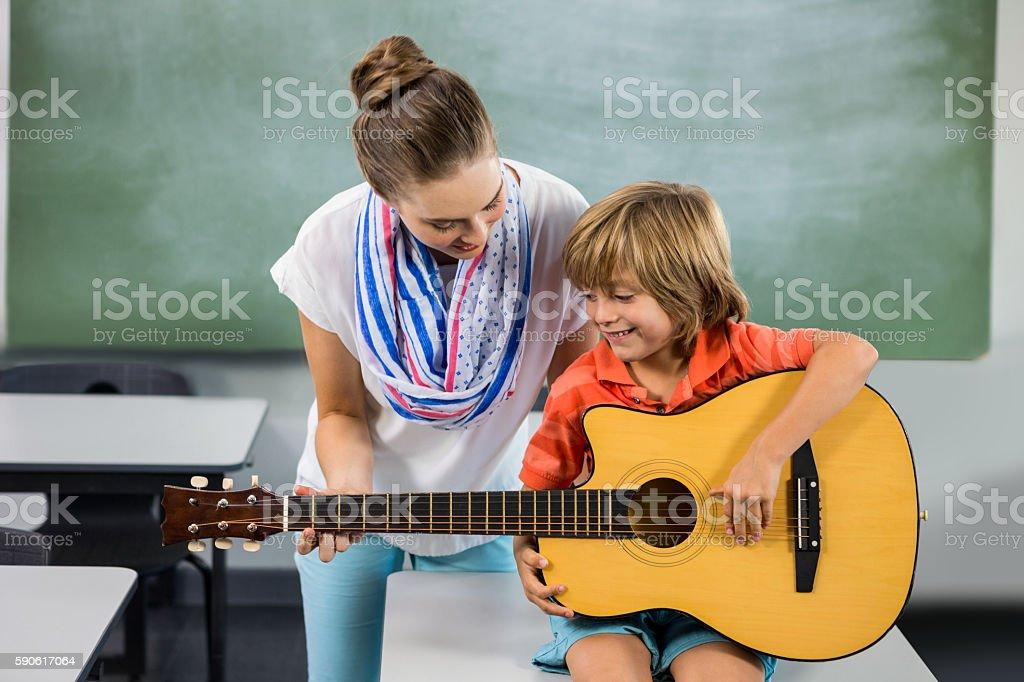 Teacher assisting boy to play guitar stock photo