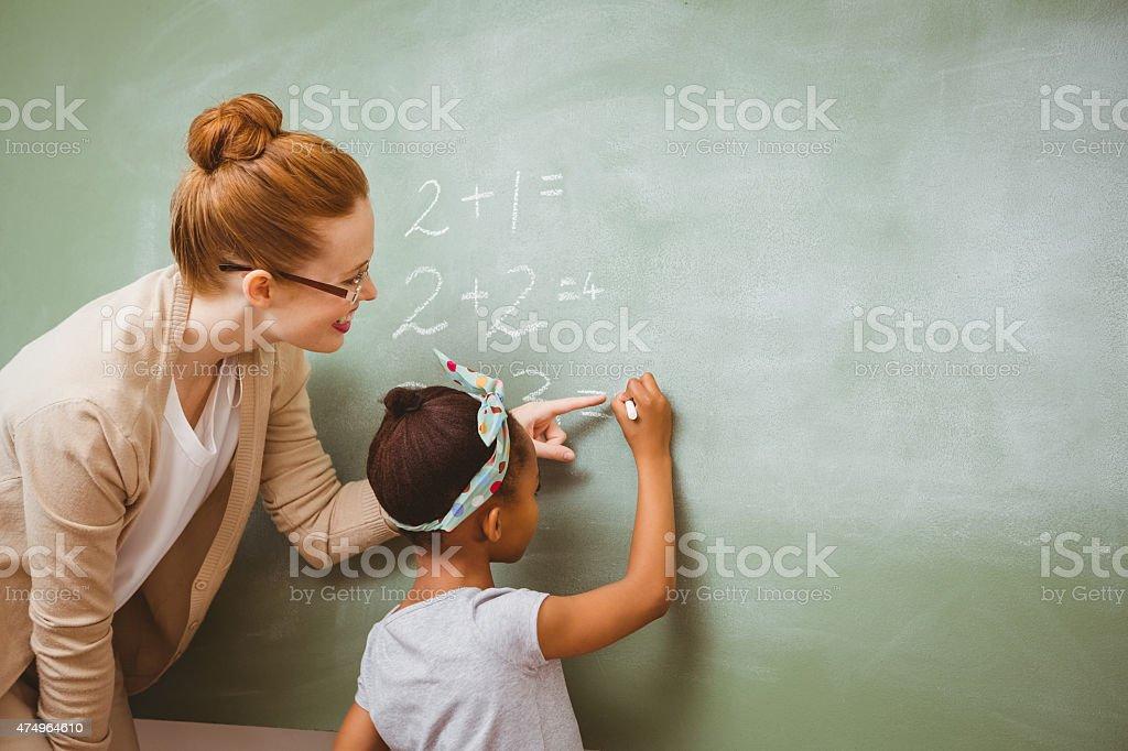 Teacher assisting girl to write on blackboard in classroom stock photo