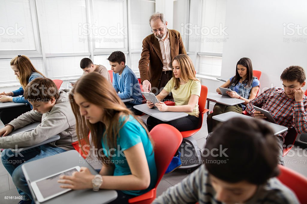 Teacher assisting high school student in a modern classroom. stock photo
