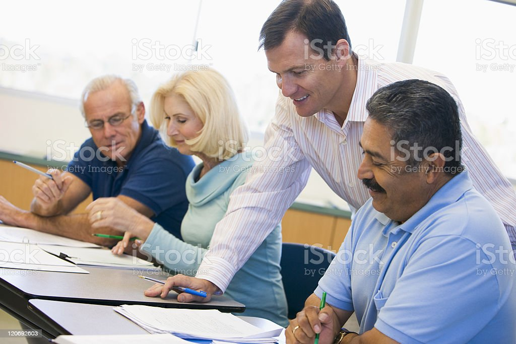 Teacher assisting mature student in class stock photo