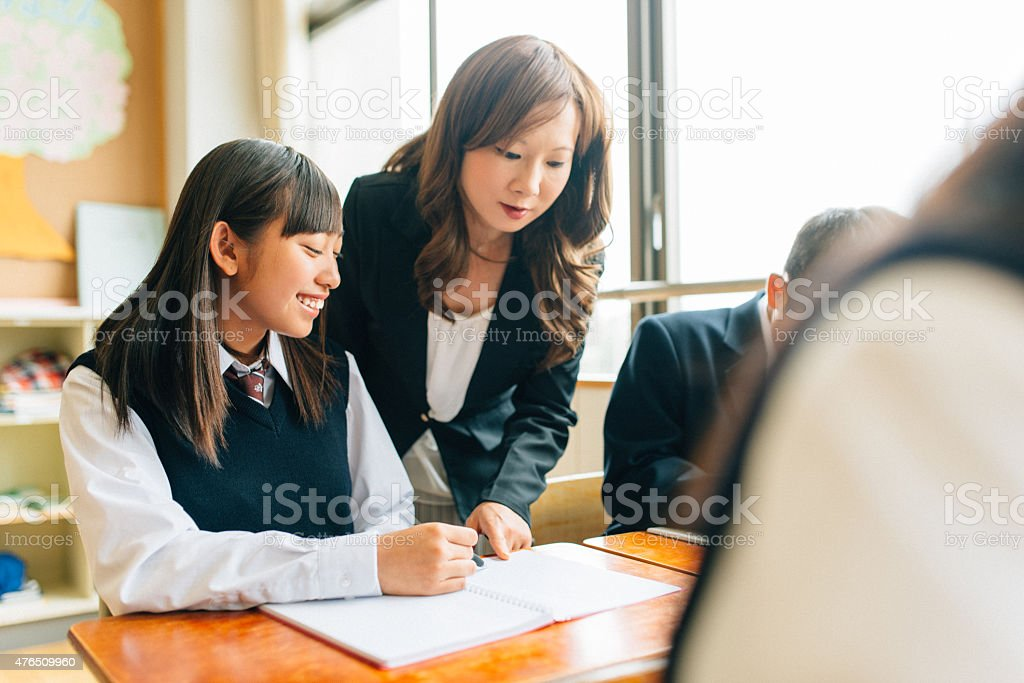 Teacher Assisting Students in Japanese Junior High School stock photo
