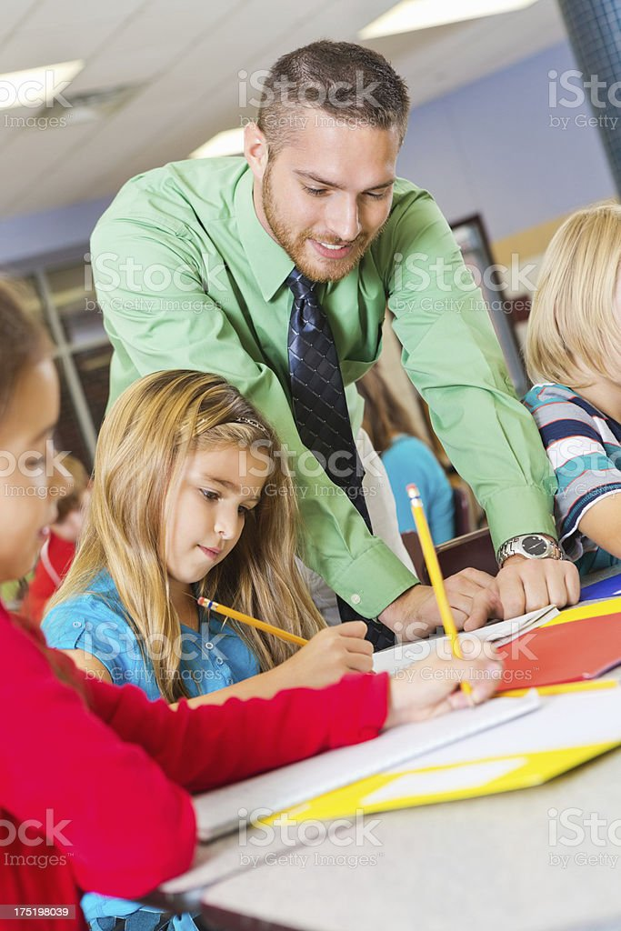 Teacher assisting young learners with schoolwork stock photo