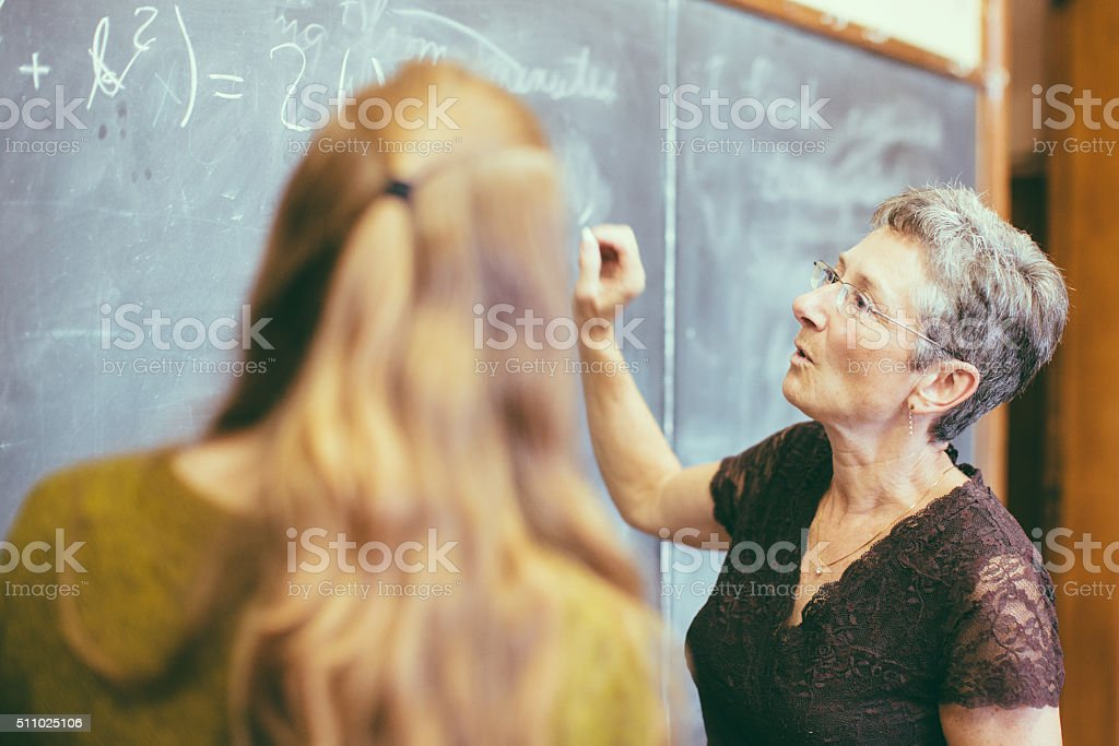 Teacher at chalkboard teaching student stock photo