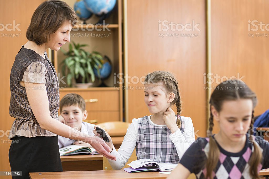 Teacher confiscating schoolkid's mobile phone at lesson stock photo