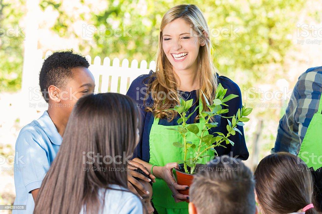 Teacher explaining gardening to elementary student during farm field trip stock photo