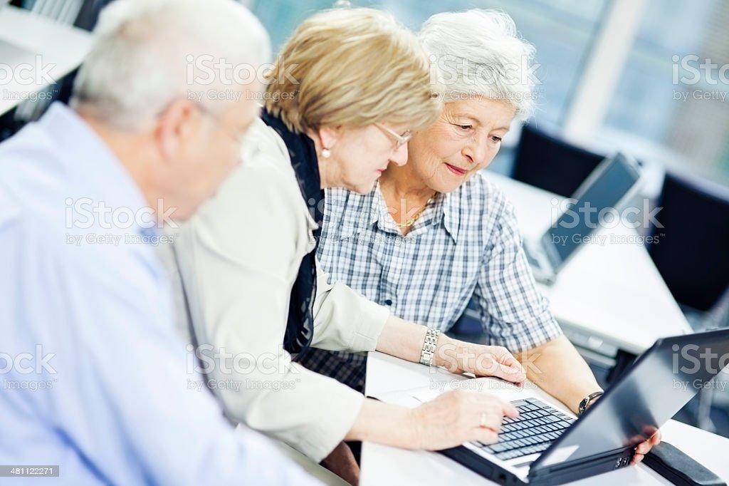 Teacher Explaining New Computer Technology to Senior Couple stock photo