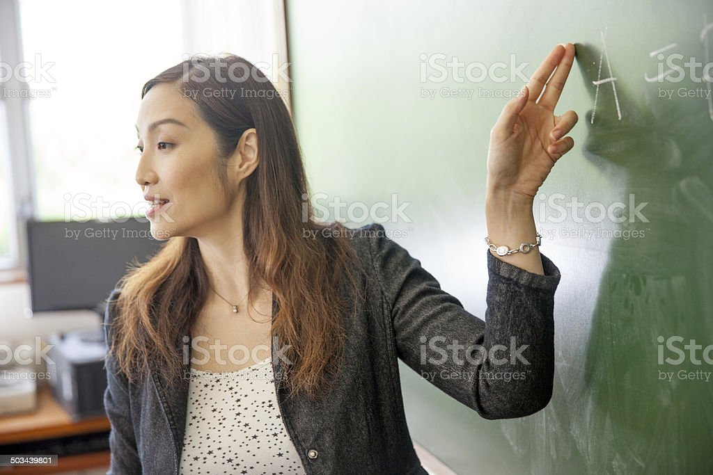 Teacher explaining the economic equation stock photo