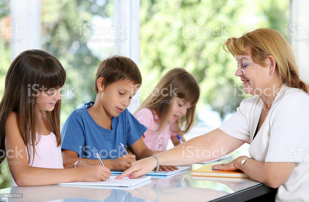 Teacher explaining the task to schoolchildren. royalty-free stock photo