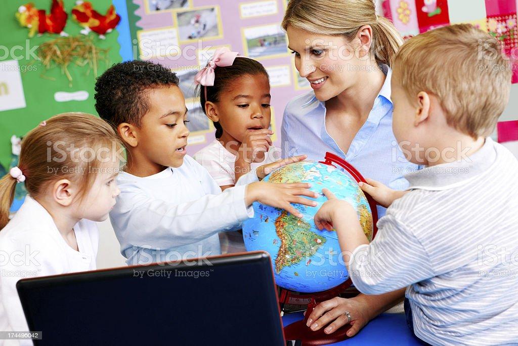 Teacher explaining the world to students royalty-free stock photo