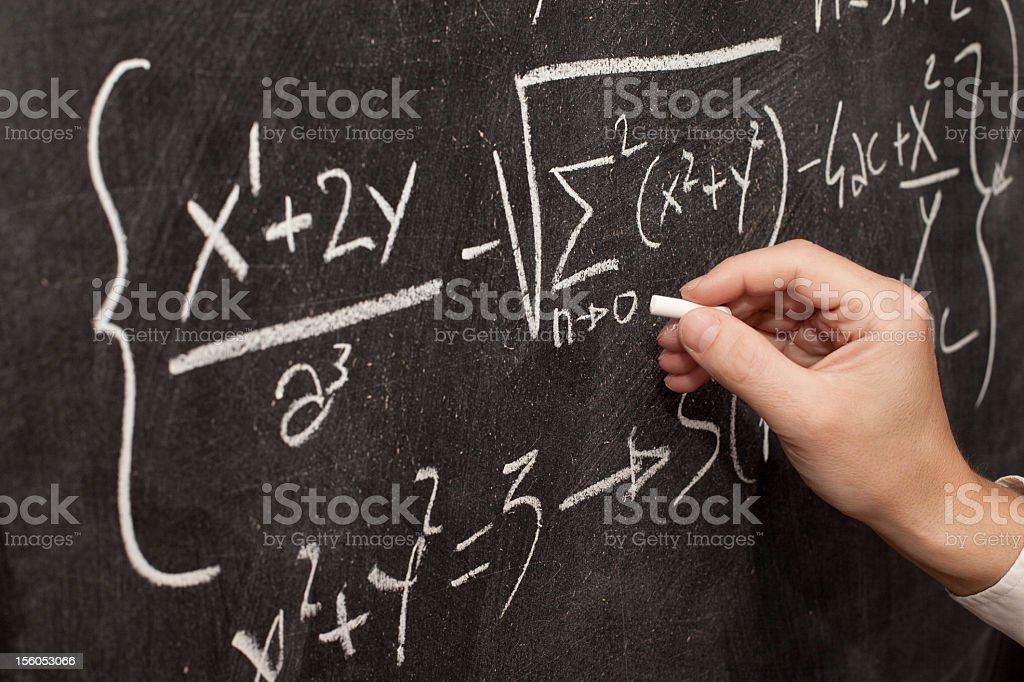 Teacher hand writing complicated math formulas on blackboard royalty-free stock photo