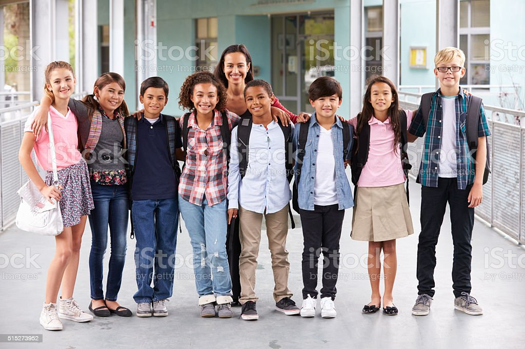 Teacher hanging out with group of elementary kids at school stock photo