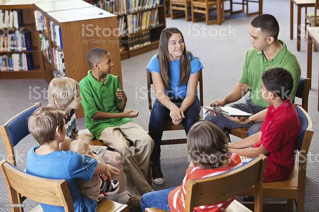 Teacher having discussion with students in library stock photo
