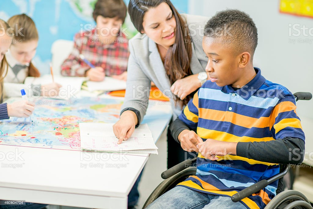Teacher Helping a Disabled Student with an Assignment stock photo