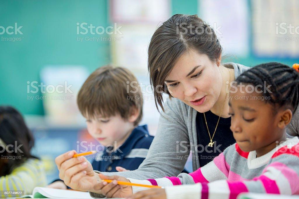 Teacher Helping a Student Understand an Assignment stock photo