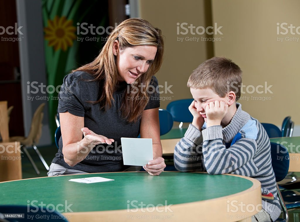 Teacher helping a young student stock photo