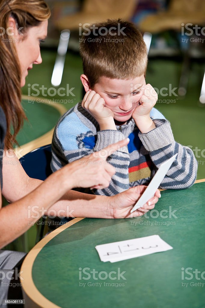 Teacher helping a young student with math stock photo