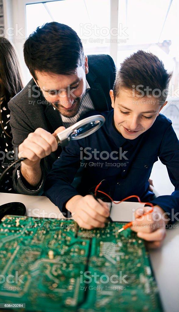 Teacher Helping Boy  In electronic  Class stock photo