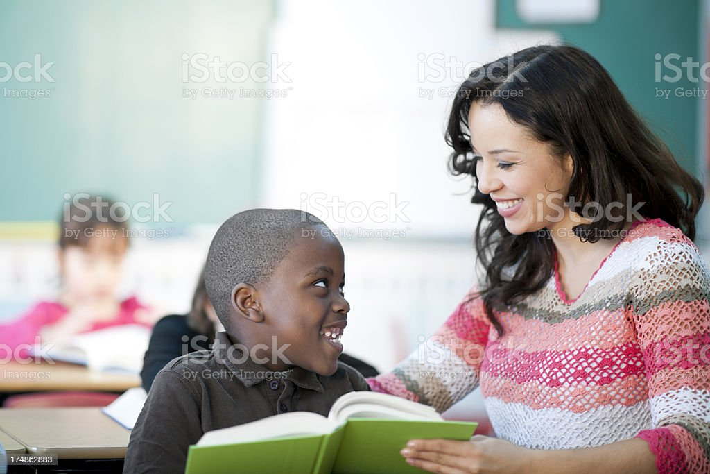 teacher helping elementary students to read stock photo