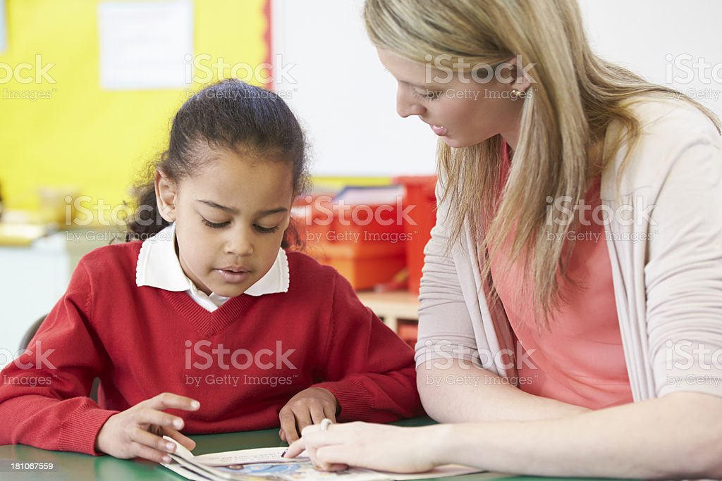 Teacher Helping Female Pupil With Practising Reading At Desk royalty-free stock photo