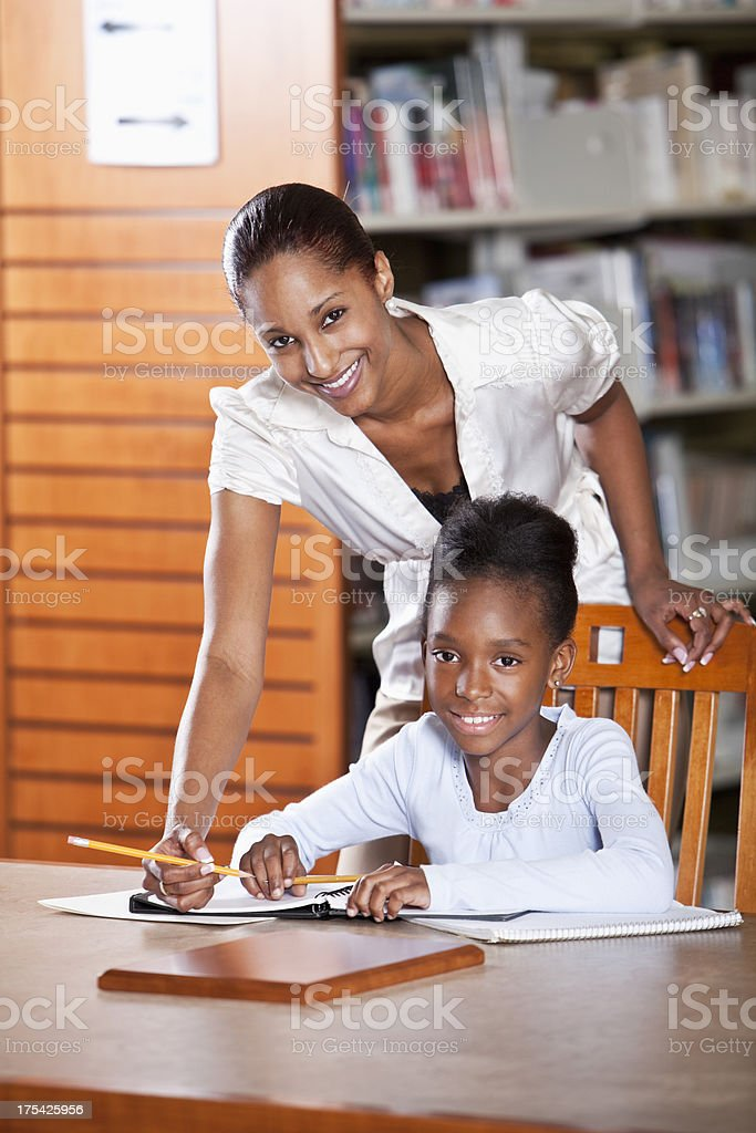 Teacher helping girl in school library royalty-free stock photo