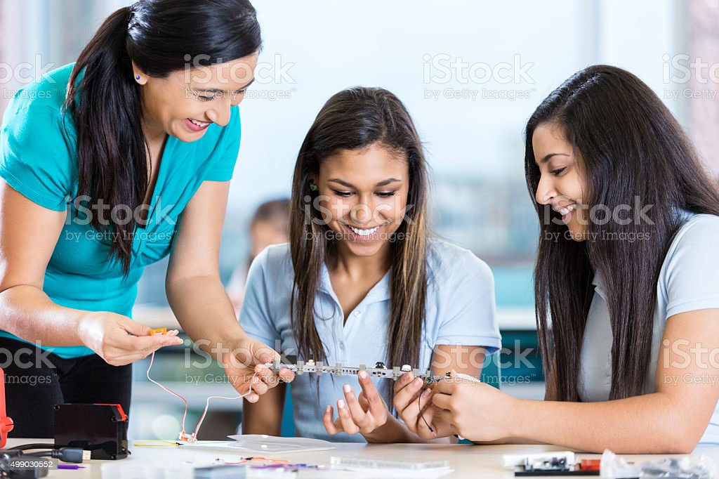 Teacher helping high school students with robotics science project stock photo
