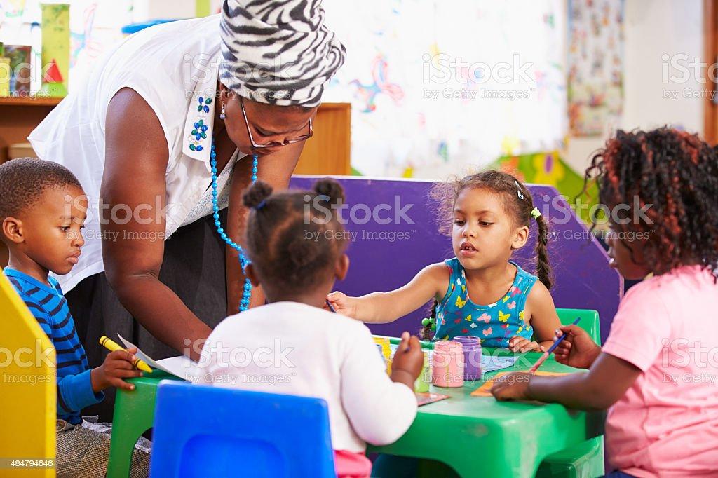 Teacher helping kids in a preschool class stock photo