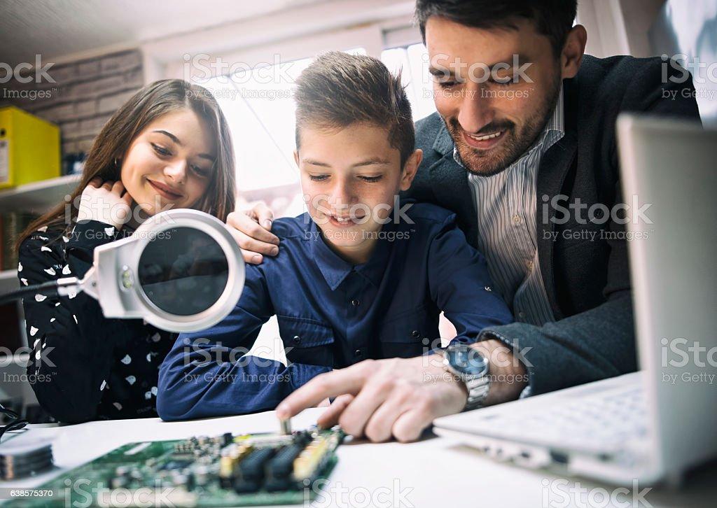 Teacher Helping kids  In electronic  Class stock photo