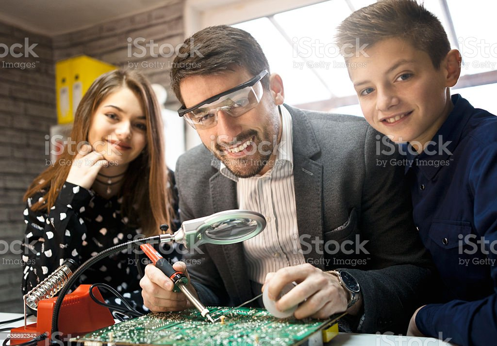 Teacher Helping kids  In electronic  Class stock photo
