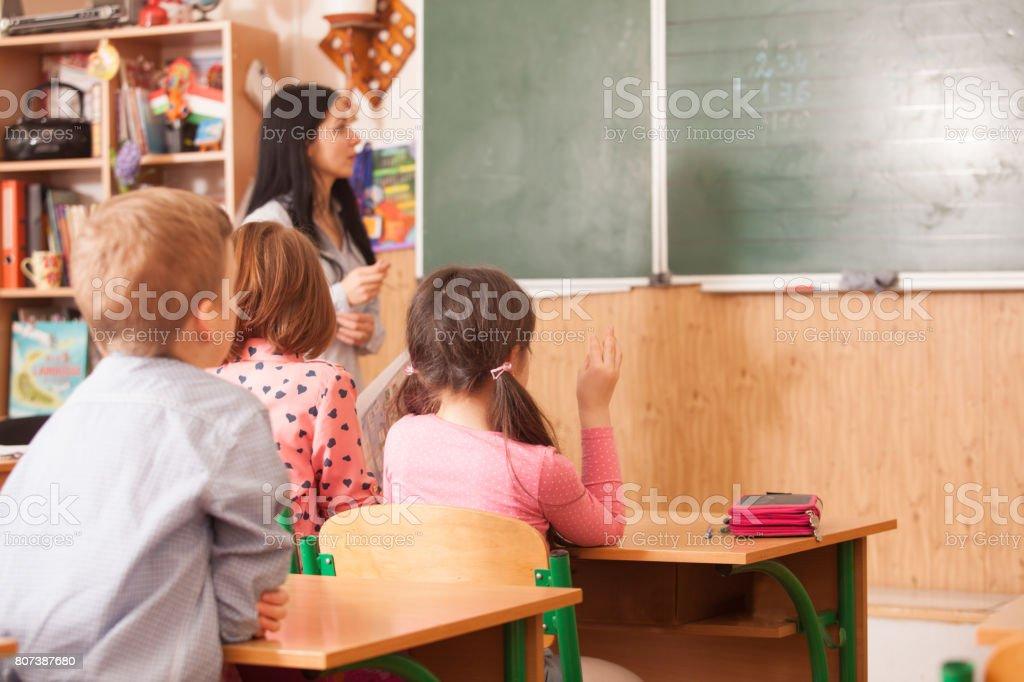 Teacher helping pupil at blackboard stock photo