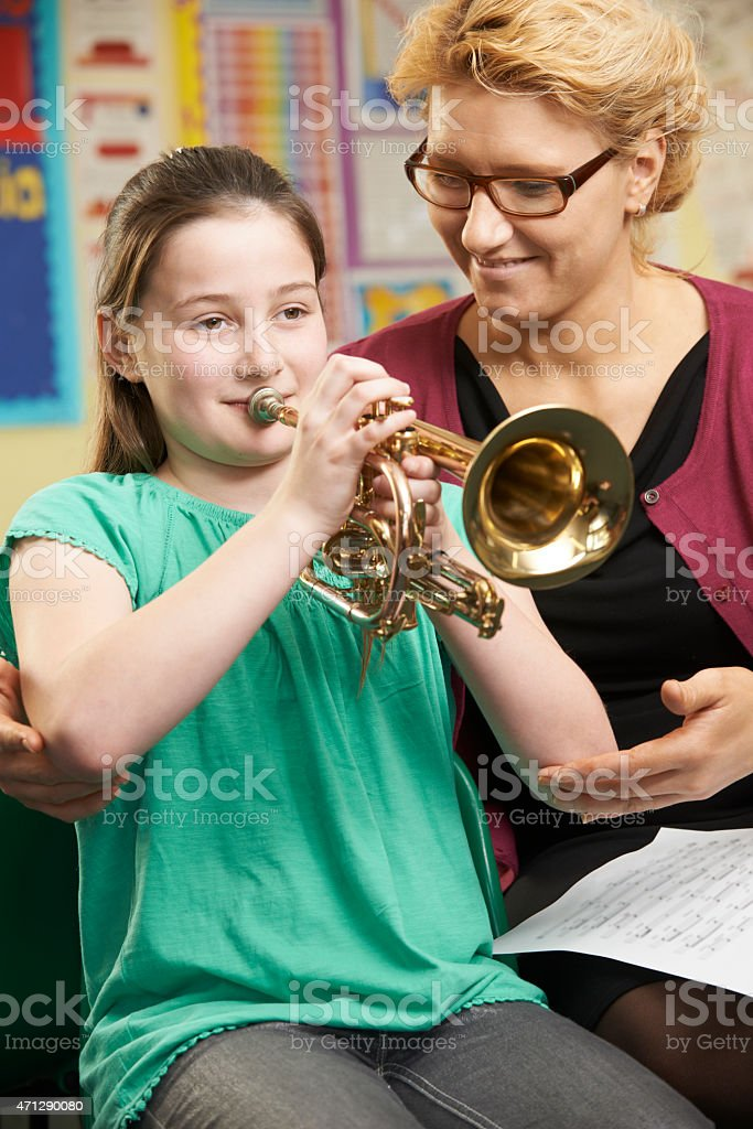 Teacher Helping Pupil To Play Trumpet In Music Lesson stock photo