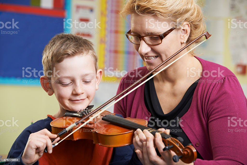 Teacher Helping Pupil To Play Violin In Music Lesson stock photo