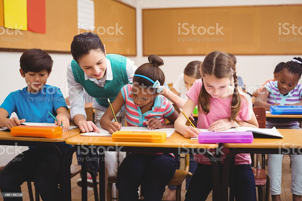 Teacher helping pupils during class stock photo
