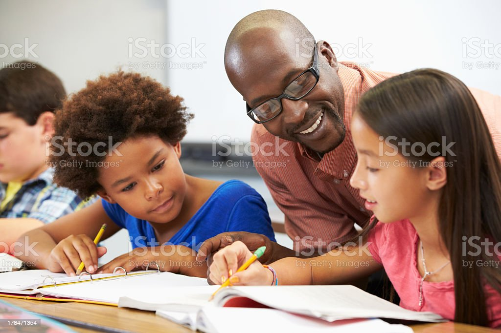 Teacher helping pupils study in the classroom stock photo