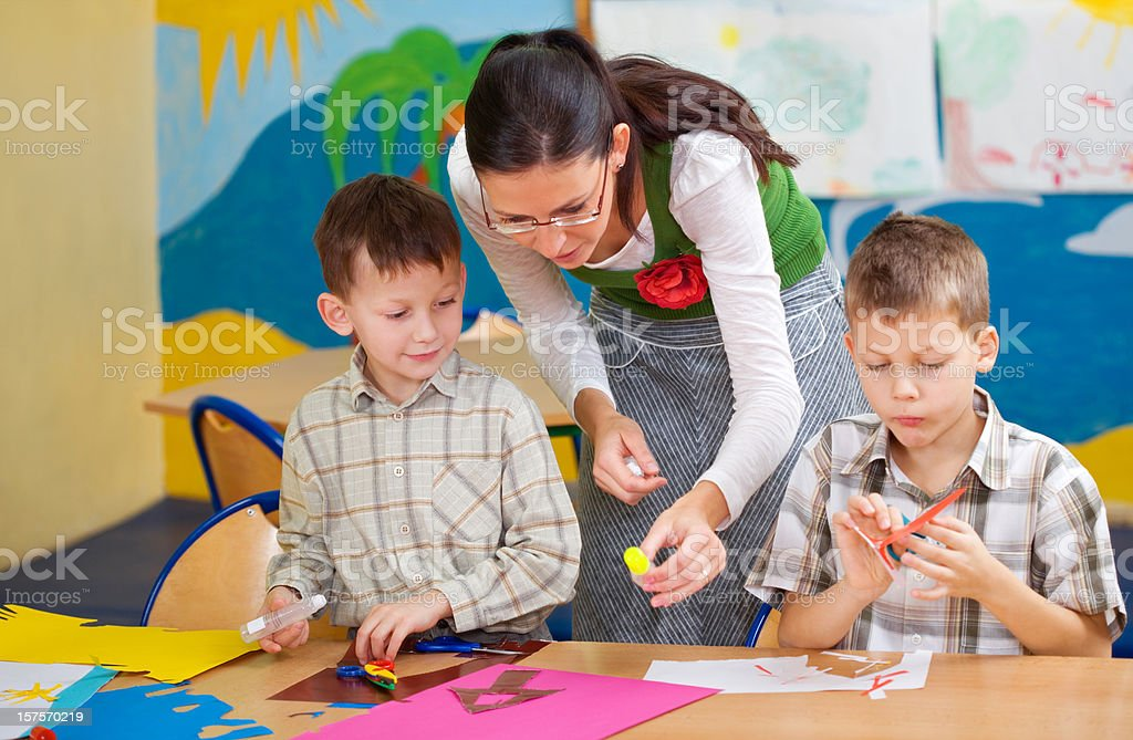 Teacher Helping Pupils With Artwork stock photo