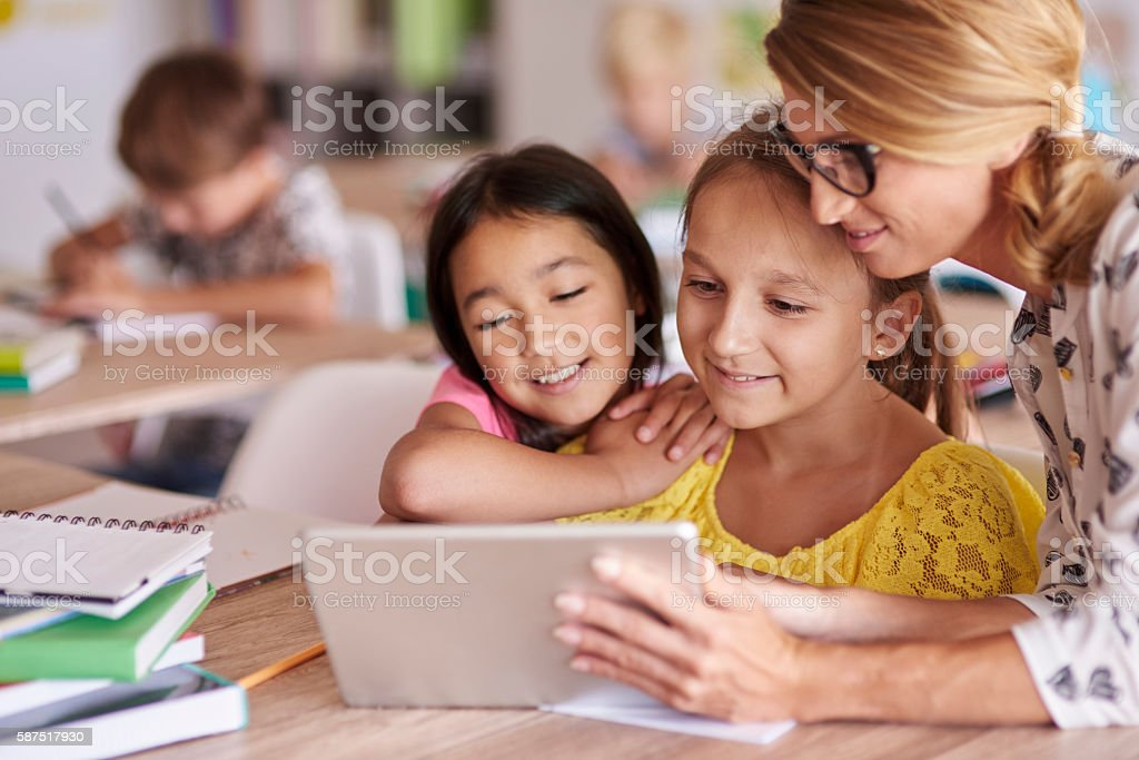 Teacher helping pupils with digital tablet stock photo