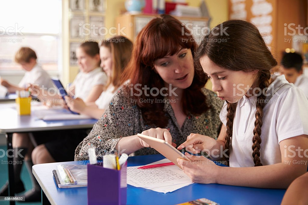Teacher helping schoolgirl using a tablet computer in class stock photo
