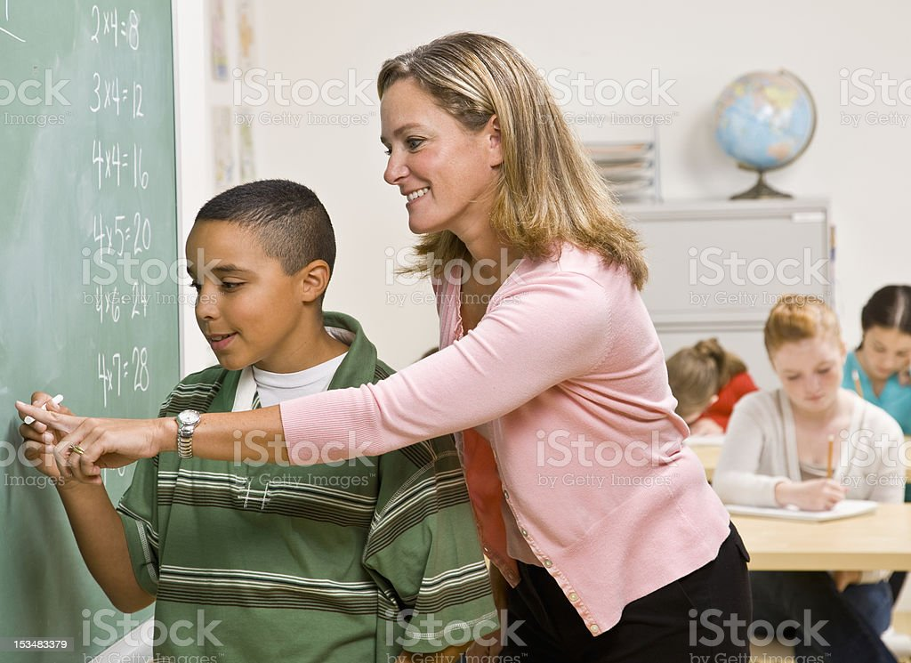 Teacher Helping Student at Blackboard royalty-free stock photo