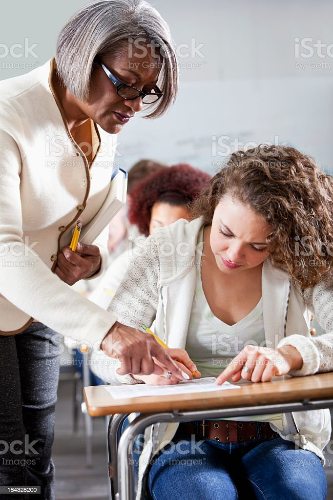 Teacher helping student in class royalty-free stock photo