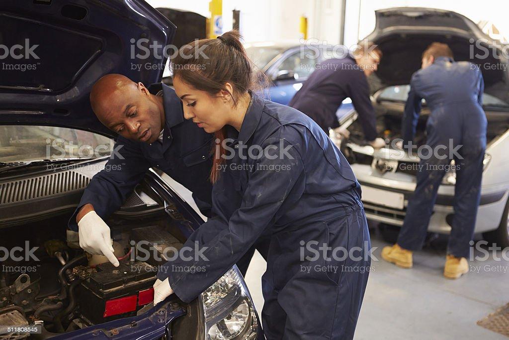 Teacher Helping Student Training To Be Car Mechanics stock photo