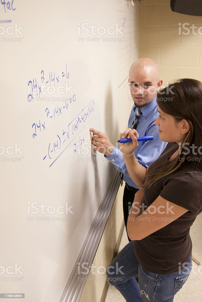 Teacher helping student with a math problem on  whiteboard. royalty-free stock photo