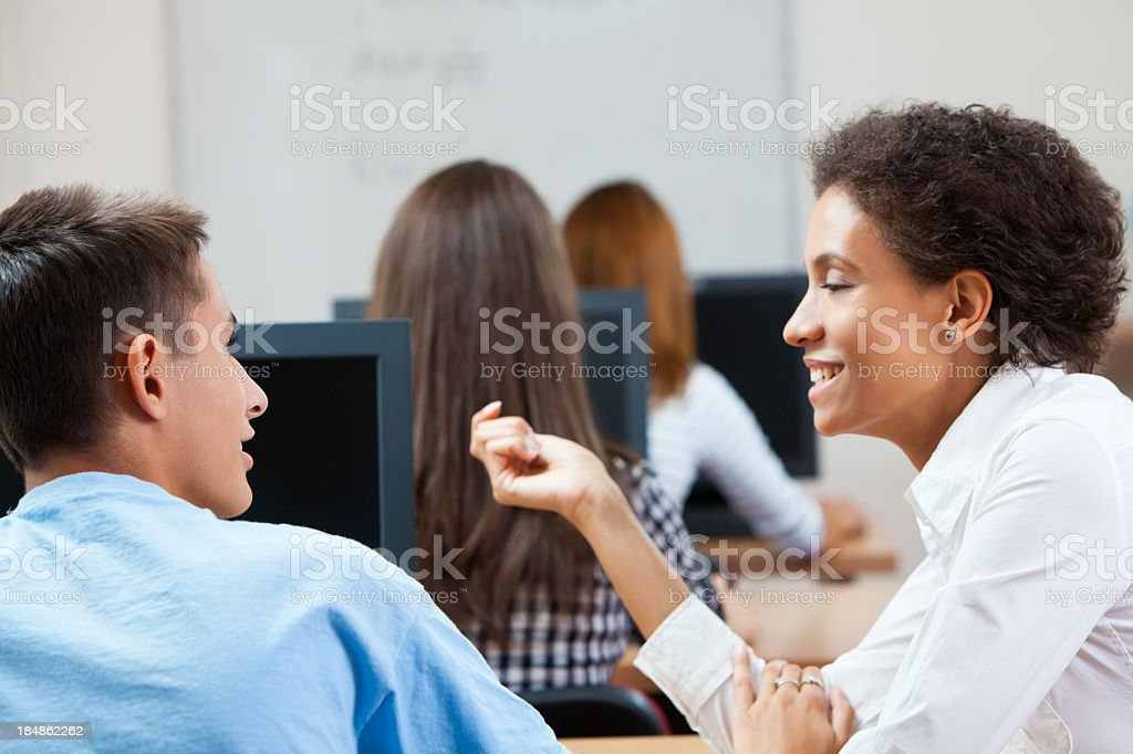 Teacher helping student with computer royalty-free stock photo
