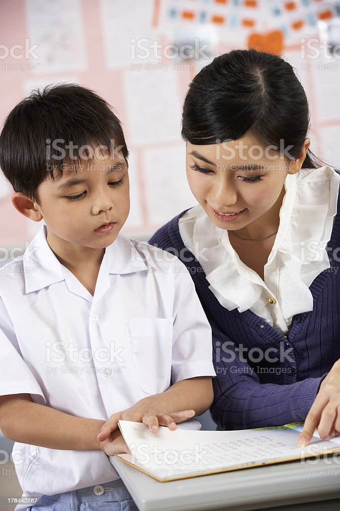 Teacher Helping Student Working At Desk In Chinese School Classroom royalty-free stock photo