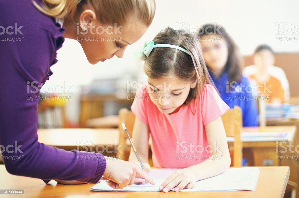 Teacher helping students in class. stock photo
