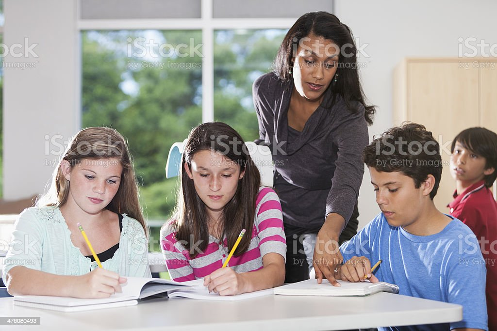 Teacher helping students in classroom stock photo