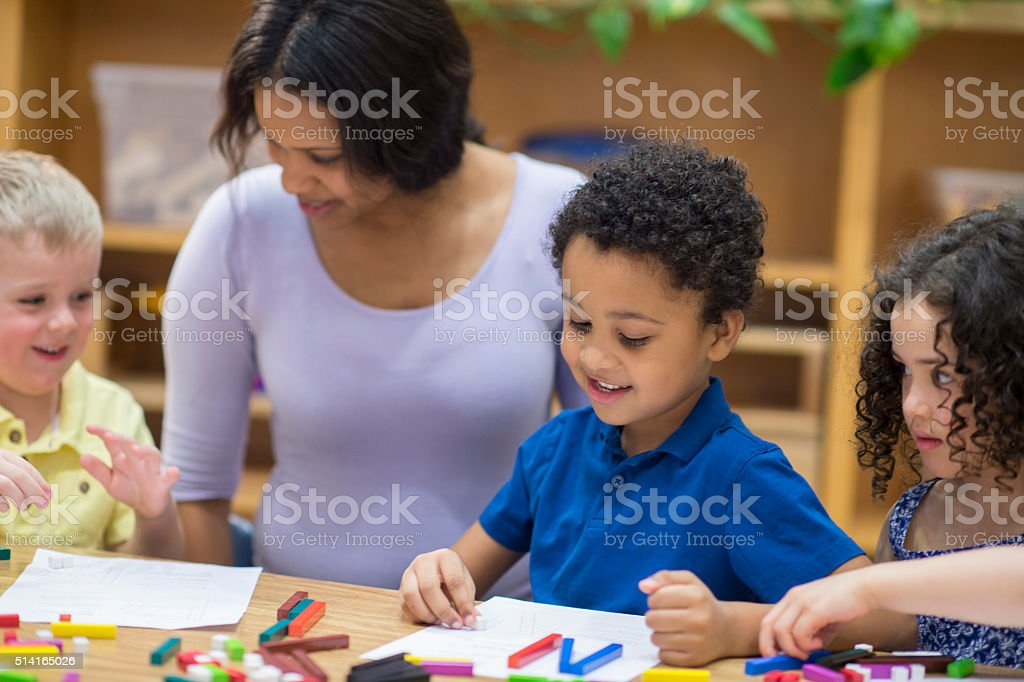 Teacher Helping Students with a Craft Project stock photo
