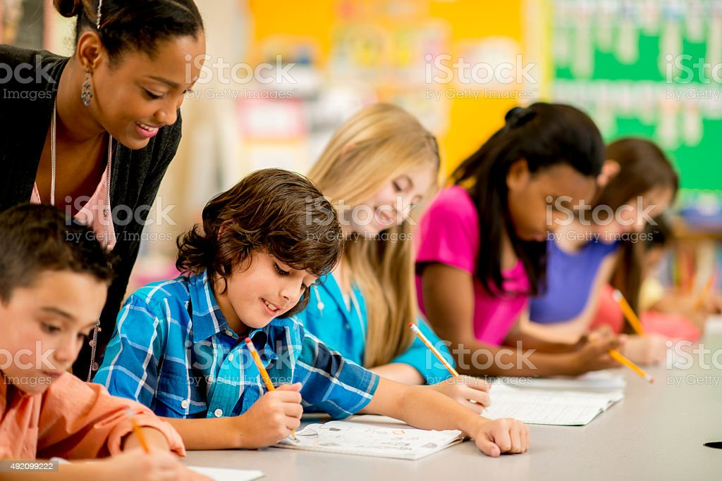 Teacher Helping Students with an Assignment stock photo