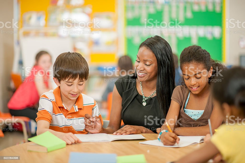 Teacher Helping Students with Questions stock photo