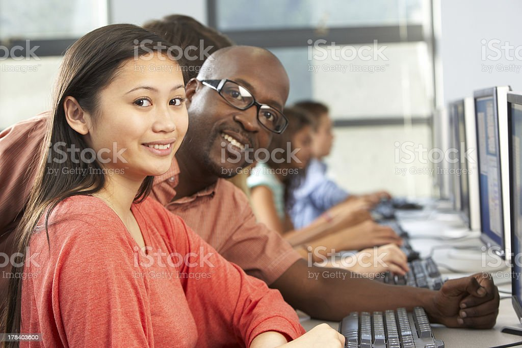 Teacher Helping Students Working At Computers In Classroom royalty-free stock photo